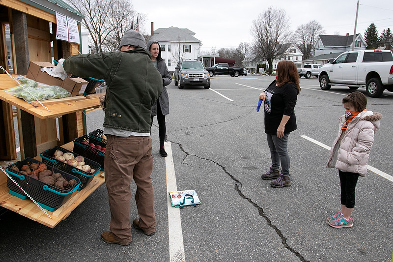 Growing Places, located at the Doyle Center in Leominster, had their Montachusett Mobile Market in the parking lot of the Leominster Veterans Center and Senior Center on Wednesday, March 25, 2020. They built this mobile market, they nicknamed The Veggie Wagon, last year and are now using it during this emergency to help bring fresh produce to anyone that needs it. They United Way helped them by donating their instant meals they make to give out, for free, at the mobile market. Volunteer Chamb Meehan gets some produce for Donna Chace and her granddaughter Shadiya Schofield, 6, both trying to practice social distancing. Waiting to ring them in is Sami Dokus the youth development and sustainability coordinator for Growning Places. SENTINEL & ENTERPRISE/JOHN LOVE