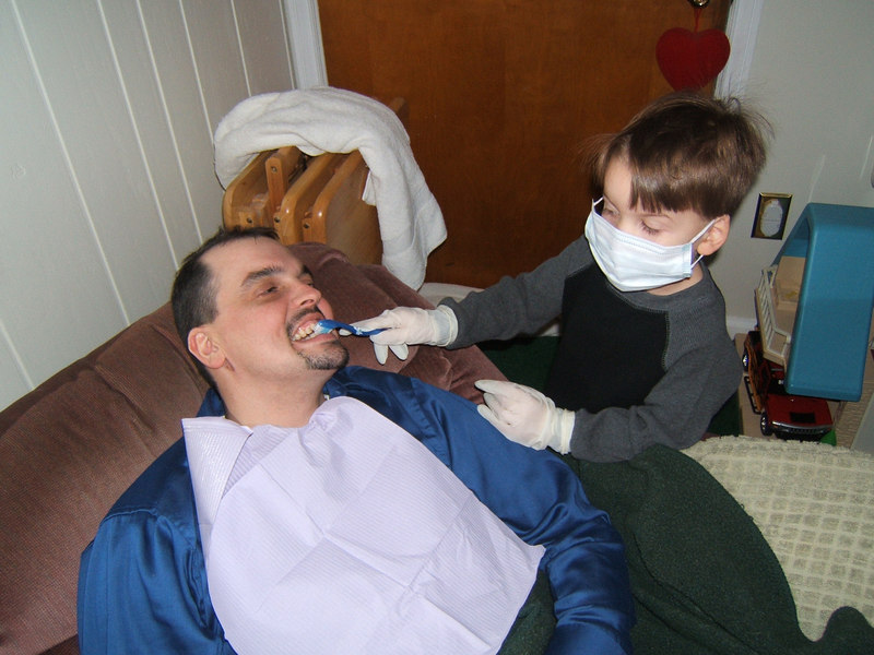 Gavin being a dentist at home and cleaning Dave's teeth.