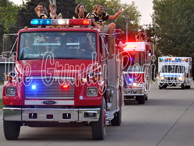 Members of the football team roll up in a fire truck during the parade.