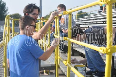 Tanner Butler, Colby Skinner, Mason Hoveland and Jacob Gould paint the bleachers during the school improvement day on Wednesday.