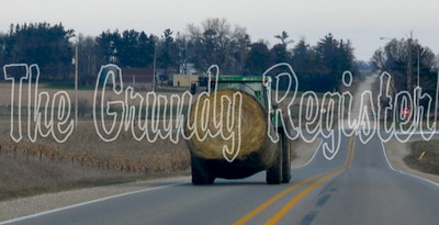 A farmer transports a hay bale on T-29 just south of the Highway 175 intersection near Grundy Center.