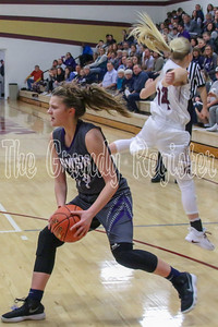 AGWSR's Grace Finger steps past Grundy Center's Maddie McMartin flying in to defend the Cougar freshman during Friday's game. (Jake Ryder/Mid-America Publishing)