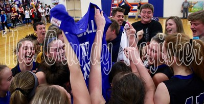 The Dike-New Hartford girls basketball team hoists its state qualifier banner as Wolverine fans rush the court after D-NH's 64-53 victory over North Linn. The Wolverines shocked the top-rated Lynx to reach the state tournament for the first time as a consolidated school district.