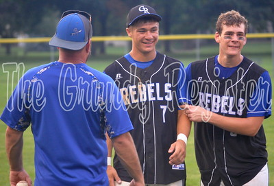 Gladbrook-Reinbeck's Walker Thede (center) and Jackson Kiburis (right) walk off the field and greet Thede's father Barry (left) after a 3-2 district final loss to Don Bosco. Thede, a multi-sport standout at G-R, made his last appearance in a Rebels uniform count with his first career home run as the Rebels nearly rallied to upend the Dons. (Rob Maharry photo)