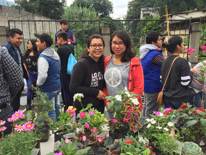 Two teachers in charge of selling the donated plants
