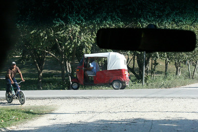 "This little red taxi is called a ""tuk-tuk"" pronounced ""took took"".  They are everywhere."