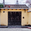 Wooden door of a yellow house in Antigua Guatemala.