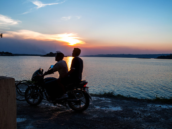 Guys on motorcycle during a sunset in Flores, Guatemala