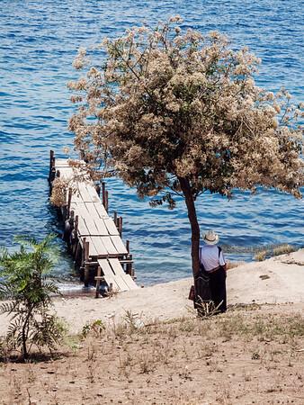 Man standing against a tree by Lake Atitlan