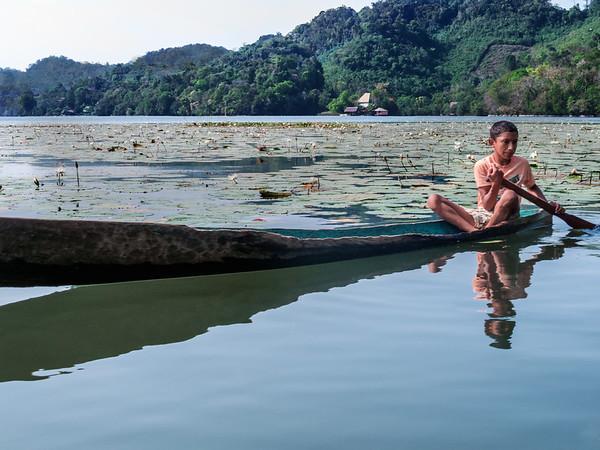 Boy in a boat on the Rio Dulce River in Guatemala
