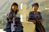 Two young girls in traditional dress pose at church cross in the village of Santa Catarina Palopo, Guatemala, Central America.