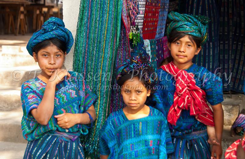 Three children in traditional dress at the market in Santa Catarina Palopo, Guatemala.