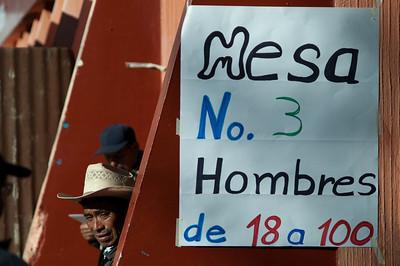 Men gather around a voting table in Huitán's urban center.