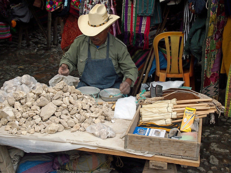 Man selling limestone rocks<br /> Heated to form lime used with<br /> corn to remove hulls