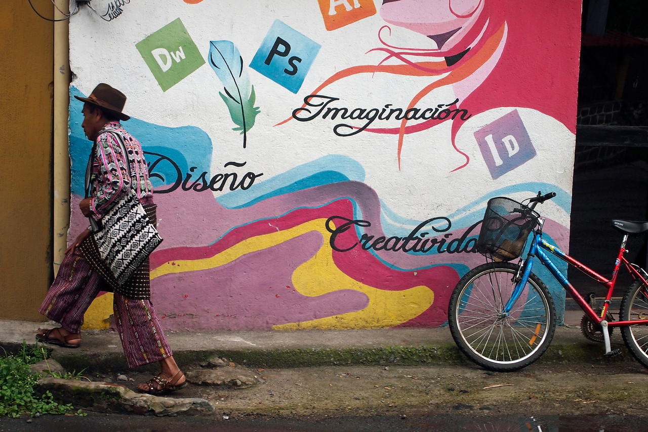 Guatemalan man wearing traditional kilt and pants - sign reads Imagination, Design and Creativity