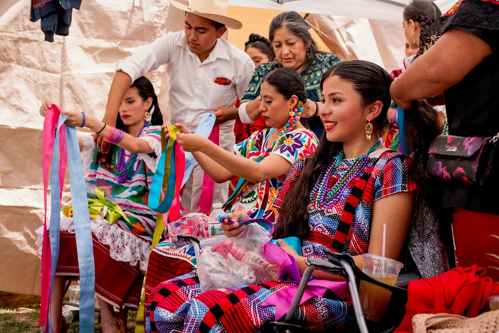 . Jazmin Gonzalez, right, Jenny Robles (center) and Paulina Magaña have ribbons braided into their hair at Viva Oaxaca Guelaguetza in San Lorenzo Park on May 20, 2018. (Kara Meyberg Guzman -- Santa Cruz Sentinel)