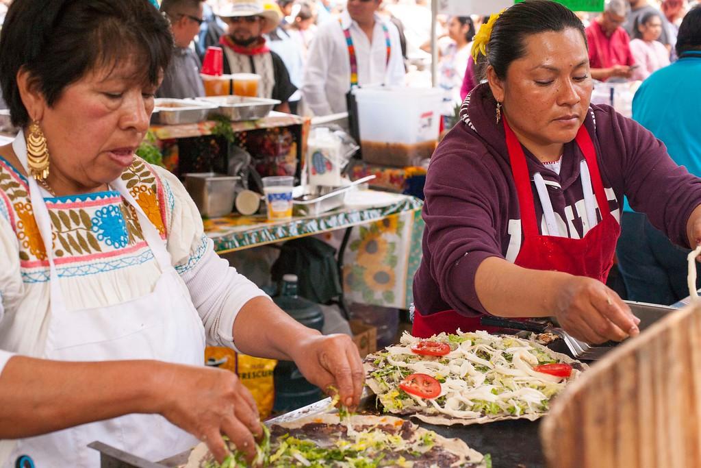 . Women prepare tlayudas in a tent at Viva Oaxaca Guelaguetza in San Lorenzo Park on Sunday, May 20, 2018. (Kara Meyberg Guzman -- Santa Cruz Sentinel)