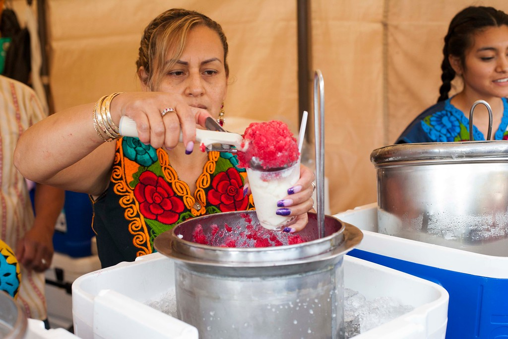 . A woman scoops a ice-cold dessert in the Ricas Nieves tent at Viva Oaxaca Guelaguetza at San Lorenzo Park in Santa Cruz on May 20, 2018. (Kara Meyberg Guzman -- Santa Cruz Sentinel)