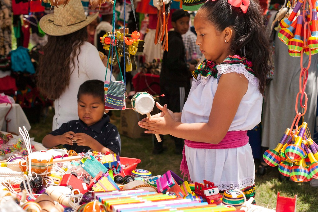 . Natalie Ramos plays with a toy in one of the tents at the Guelaguetza in Santa Cruz on Sunday, May 20, 2018 (Kara Meyberg Guzman -- Santa Cruz Sentinel)
