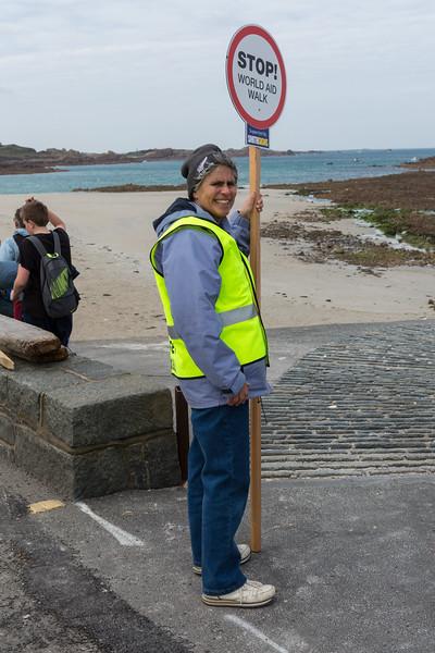 Guernsey World Aid Walk volunteer directs walkers along Cobo beach