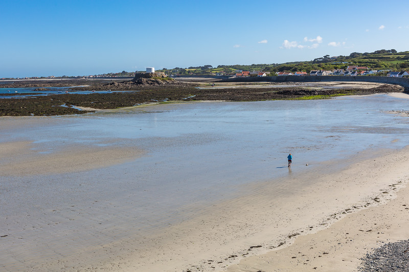 A loner walker on the sea shore at Rocquaine Bay, Guernsey
