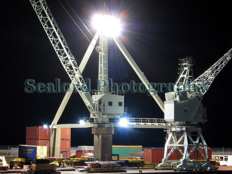 I tried to crop this image to remove the large flood light but preferred the image uncropped.  These large St Peter Port harbour cranes look like toys.  Photographed at 2200 on 1 November 2006.  Photographed by placing the camera on a wall with a 8 second time exposure and a two second shutter delay. At the time of photography it was windy so I had to place the camera in the corner of two walls to prevent camera movement.<br /> File No. 011106 4208<br /> ©RLLord<br /> fishinfo@guernsey.net