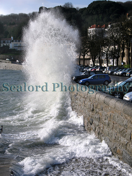 This image was taken about 15 minutes after high water as a wave breaks against the granite wall protecting the coast road from Havelet Bay.  Several waves did crash over the wall and seawater flowed to the opposite side of the road but the road remained open.  High tide was forecast for 0815 at 9.8 metres but due to a low barometric pressure of 973 mb Hg the tide rose to a height of 10.7 metres according to Captain Peter Gill, St. Peter Port's harbour master.  The wind was blowing from the south-west so the east coast was protected from the worst weather.  Captain Peter Gill informed me that in 1948 the tide reached a height of 11.3 metres in St. Peter Port when the wind blew from the south-east.  At that time the sea rose high enough to complete cover some of the St. Peter Port harbour quays.<br /> File No. 100308 3556<br /> ©RLLord<br /> fishinfo@guernsey.net