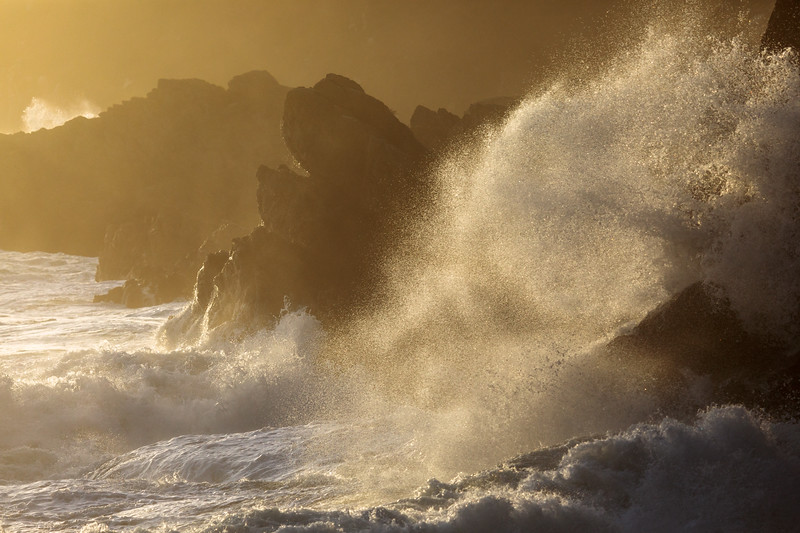 Waves and sea spray on the sea shore at Petit Port in late afternoon light