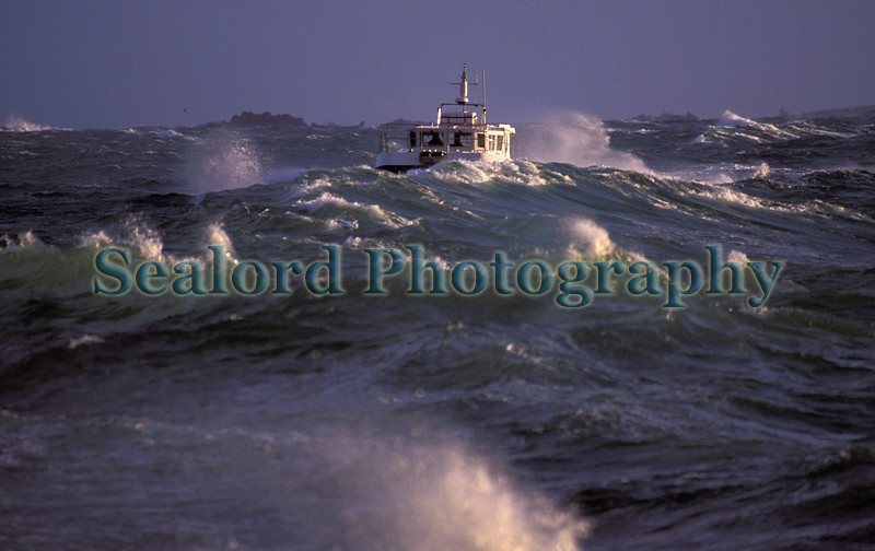During a southerly gale on the 2 December 2005 a boat ploughs through a rough sea to reach the safety of St. Peter Port harbour, Guernsey.  Photographed from the shore near Castle breakwater, St. Peter Port harbour, Guernsey<br /> File No. 021205 29-805<br /> ©RLLord<br /> fishinfo@guernsey.net