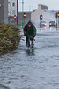 Cycling through flooded St Georges Esplanade, St Peter Port, Guernsey