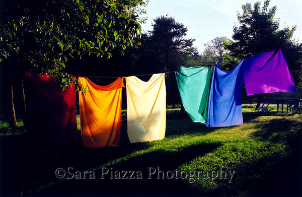 "Rainbow Clothesline. This is my actual clothesline in Edgartown. My Sunday school teaching kit for years included these two-yard swatches of color; used for king's robes, water, grass, sky, sea, as well as various other story-telling props, or even for a classroom-sized rainbow, stretched from one side of the room to the other. One gray Vineyard day I thought, ""I need a rainbow.""  I noticed the cloths, retired and folded up on my bookshelf, and decided to make myself a rainbow on my clothesline. I then realized, ""What day don't  I need a rainbow?"" So I left it there for a couple of years, until the cloths finally frayed, faded and wore out. I made a 2' x 3' poster of this image that hangs on my Brookline kitchen wall."