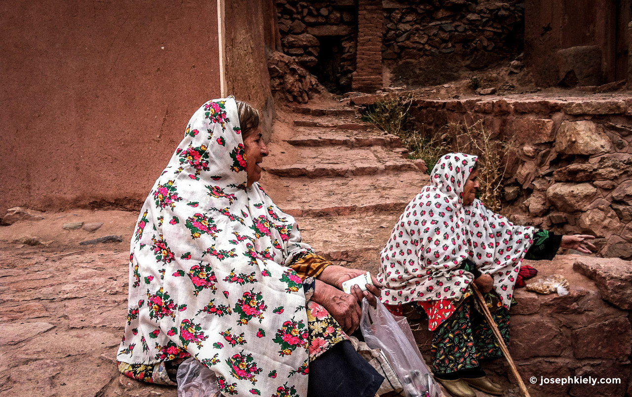Two woman sitting on steps in the city of Abaneh Iran