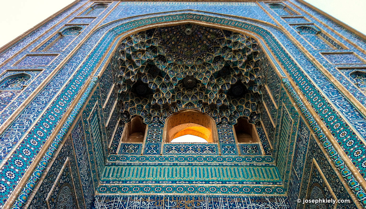 Looking up at the intricate and ornate blue tiled entrance to the Masjed-e Jameh Mosque in Yazd Iran