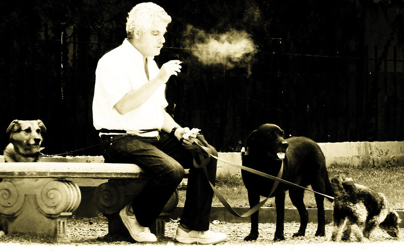 A man stops walking the dogs to enjoy a smoke - Buenos Aires, Argentina.