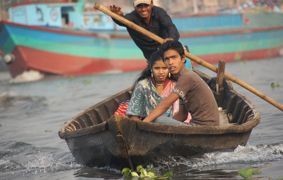 A smiling oarsman transports passengers along the ever chaotic Buriganga River.