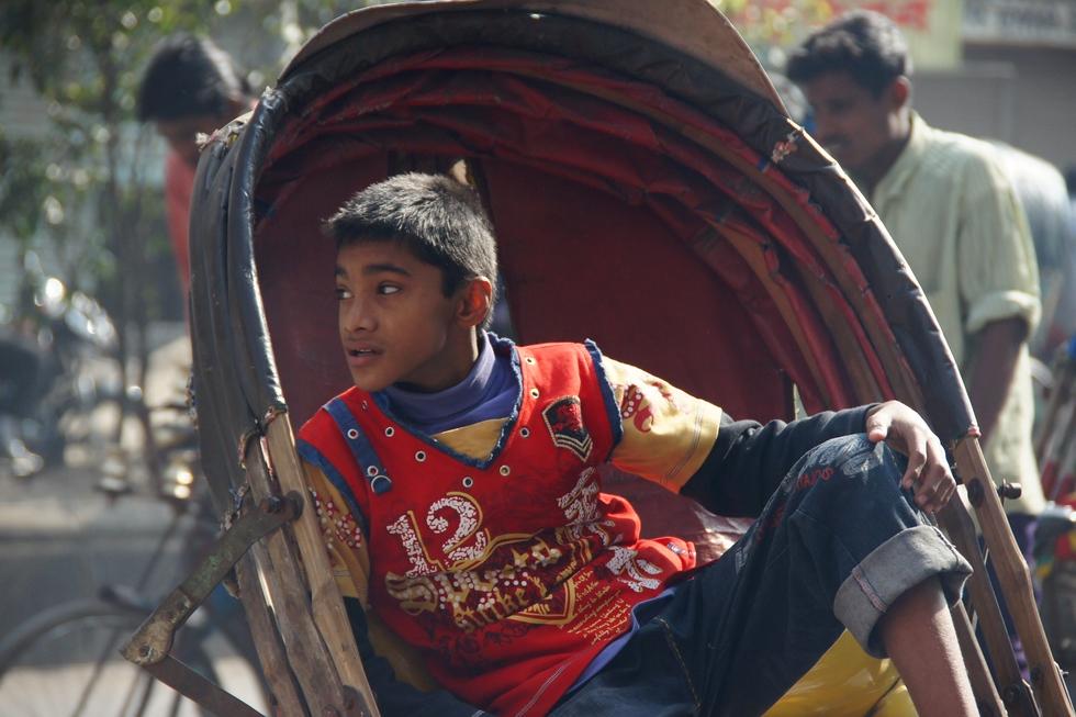 This Bangladeshi boy rests in a rickshaw.