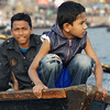 This is a telephoto shot from the Buriganga river where a group of boys and young men enjoy a boat ride.