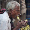 This Bangladeshi man sits down to enjoy a refreshing sugarcane snack.