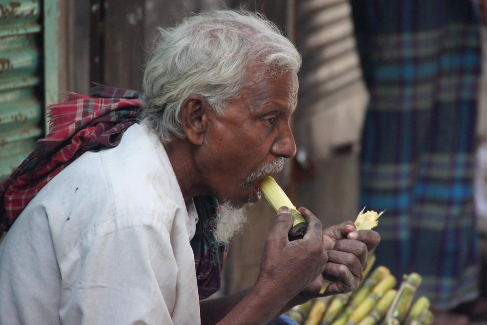 This Bangladeshi man sits down to enjoy a refreshing sugarcane snack.