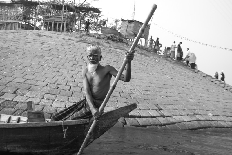 In this black and white photo, I had just boarded a small vessel to cruise down the Buriganga river when I encountered this oarsman with a distinct face.