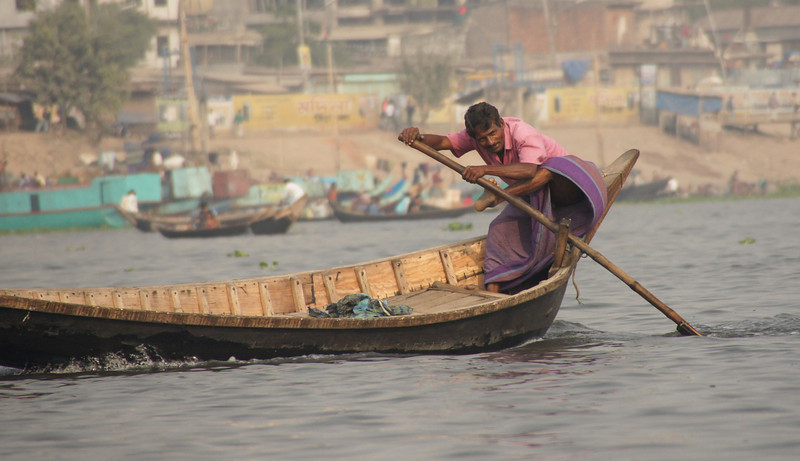 This oarsman wearing longyi was one of many small vessel operators nearby the Sadarghat.