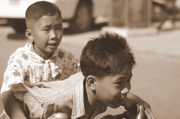 These two boys race down the streets on their bike with enthusiasm that is only found in youth - Siem Reap, Cambodia.