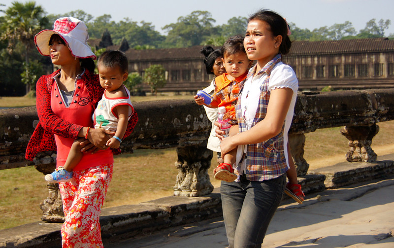 Two ladies carrying children walk around just outside the entrance to Angkor Wat, Cambodia.