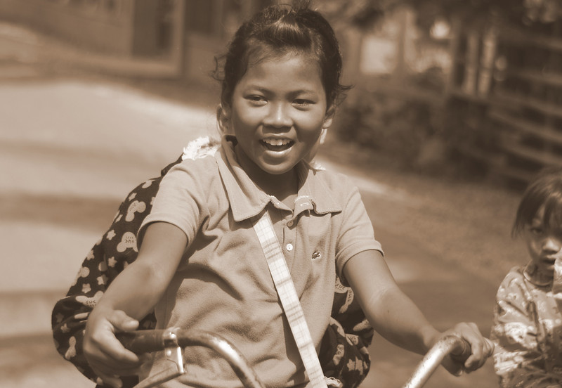 A girl exuberantly smiles as she peddles her bike with a mate on the back - Battambang, Cambodia.