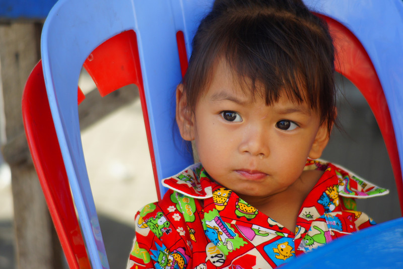A Khmer child sits on a blue and red plastic chair waiting patiently for some food to be delivered for lunch - Battambang, Cambodia.