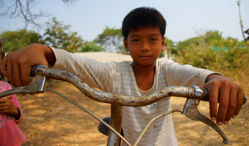 A friendly boy poses on his bicycle while grasping both the handle bars in a close up photo  - Battambang, Cambodia.