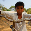 A friendly boy poses on his bicycle while grasping both the handle bars in a close up photo  - Battambang, Cambodia.