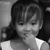 A cute girl raises her hand close to her mouth before she can fully crack a smile - Battambang, Cambodia.