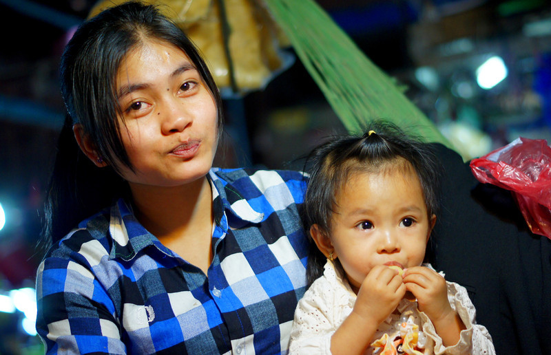 A proud mother poses with her daughter in a local market - Siem Reap, Cambodia.