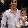 A Khmer man carrying his daughter willingly smiles and poses for this particular photo - Battambang, Cambodia.